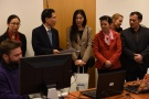 Powiększ zdjęcie: Na zdjęciu widać uczestników spotkania skupionych wokół komputera i słuchających wyjaśnień naukowca.