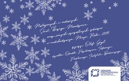 Na zdjęciu widać kartkę z życzeniami, na granatowym tle białe gwiazdki śnieżne.