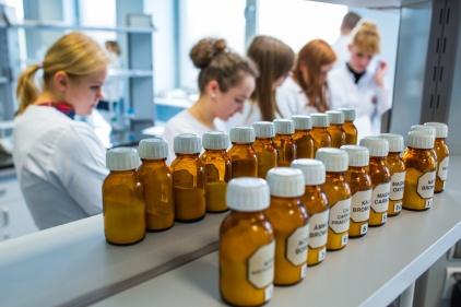 Na zdjęciu widać grupę studentek pochylonych nad probówkami, podczas doświadczeń chemicznych, w laboratorium.