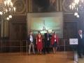 Powiększ zdjęcie: Na zdjęciu widać grupę 4 osób z tabliczką z nagrodą, w dużej sali reprezentacyjnej, na tle rzutnika.