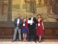 Powiększ zdjęcie: Na zdjęciu widać grupę 4 osób z tabliczką z nagrodą, w dużej sali reprezentacyjnej, na tle obrazu.