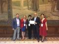 Powiększ zdjęcie: Na zdjęciu widać grupę 5 osób z tabliczką z nagrodą, w dużej sali reprezentacyjnej, na tle obrzu.