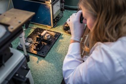 Na zdjęciu widać kobietę oglądającą próbkę przez mikroskop.