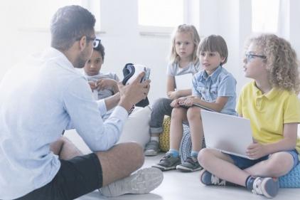 Na zdjęciu widać grupkę dzieci siedzącą na pufach i oglądającą okulary do animacji 3D, pokazywane im przez młodego mężczyznę.