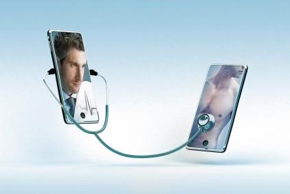 Zdjęcie przerstawia dwa telefony połączone stetoskopem - na jednym wyświetlony jest lekarz a na kolejnym pacjent.